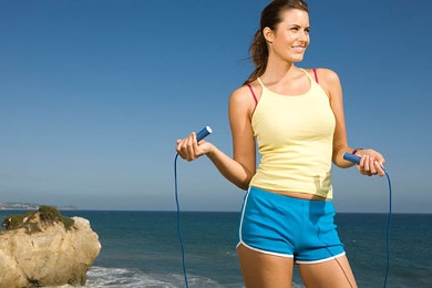 Young woman holding skipping rope on beach, smiling
